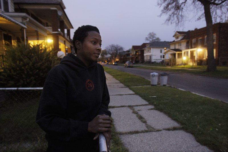 """Cassandra Cabil stands in shadows cast by her Highland Park, Mich., home as she looks out into her street, which is illuminated only by house lights. The 2.2-square-mile city removed two-thirds of its street lights because it was unable to pay its $80,000 per month light bill. """"It's pretty ghetto,"""" says Cabil. """"There's a lot of vandalism going on."""""""
