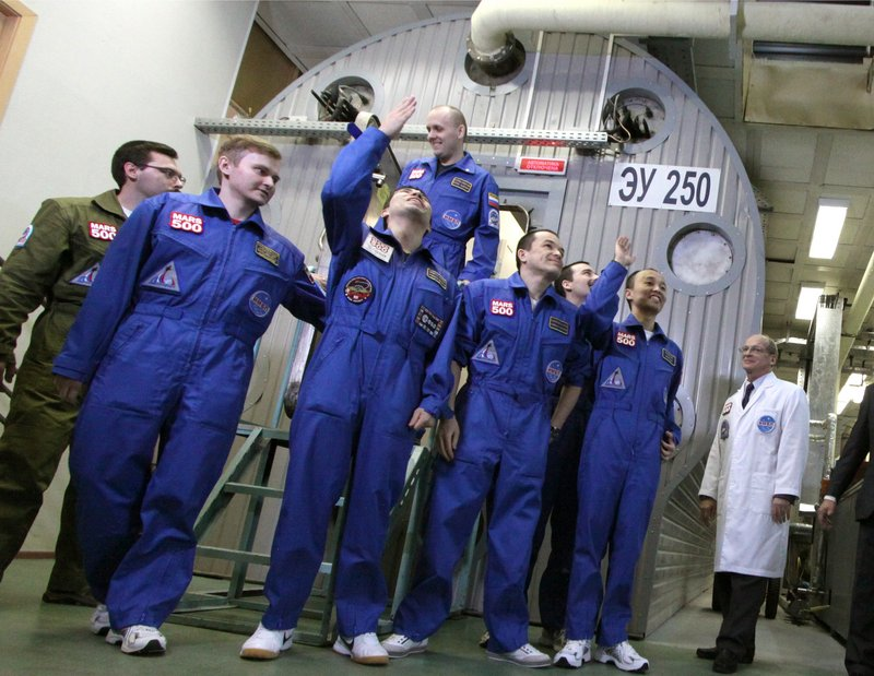 An international crew poses outside a set of windowless modules after a grueling 520-day simulation of a flight to Mars on Friday in Moscow. The all-male crew of three Russians, a Frenchman, an Italian-Colombian and a Chinese successfully completed the experiment intended to simulate the constricted and isolating conditions of space travel.
