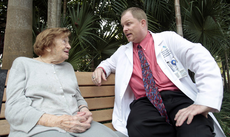 Dr. Brian Kiedrowski, right, talks to one of his patients, Victoria Cohen, 100, in Miami.