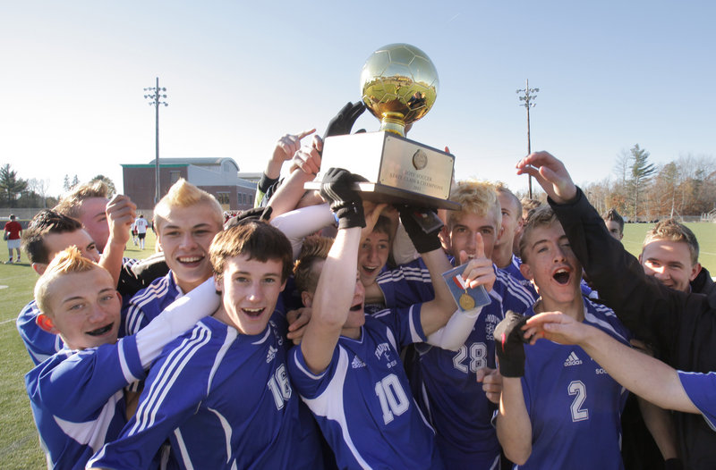 Game over, title won, and Andrew Murry, 10, the Falmouth co-captain, lifts the Gold Ball with his teammates after the Yachtsmen captured the Class B boys soccer state championship with a 2-1 victory Saturday at Hampden Academy that sent Camden Hills to its only loss of the season.