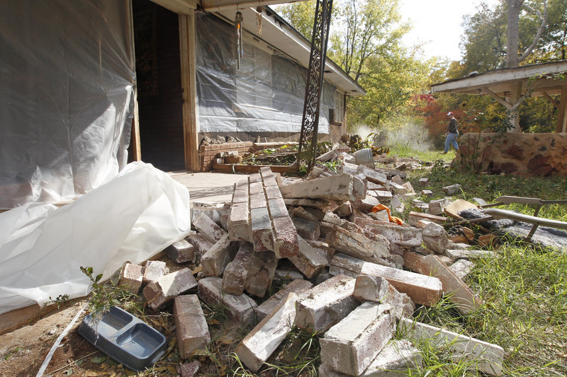 Chad Devereaux cleans up bricks Sunday that fell from his in-laws' home in Sparks, Okla., after two earthquakes hit the area in less than 24 hours. The state has experienced a dramatic increase in quakes, from about 50 a year before 2009 to 1,047 last year.