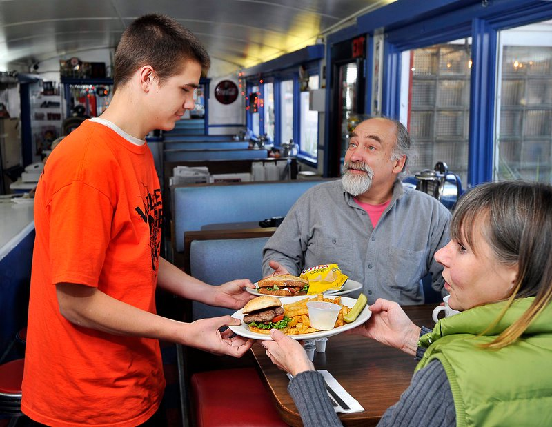 Server Logan Dewey brings Lincolnville residents Tom Sadowski and Janis Kay their orders.
