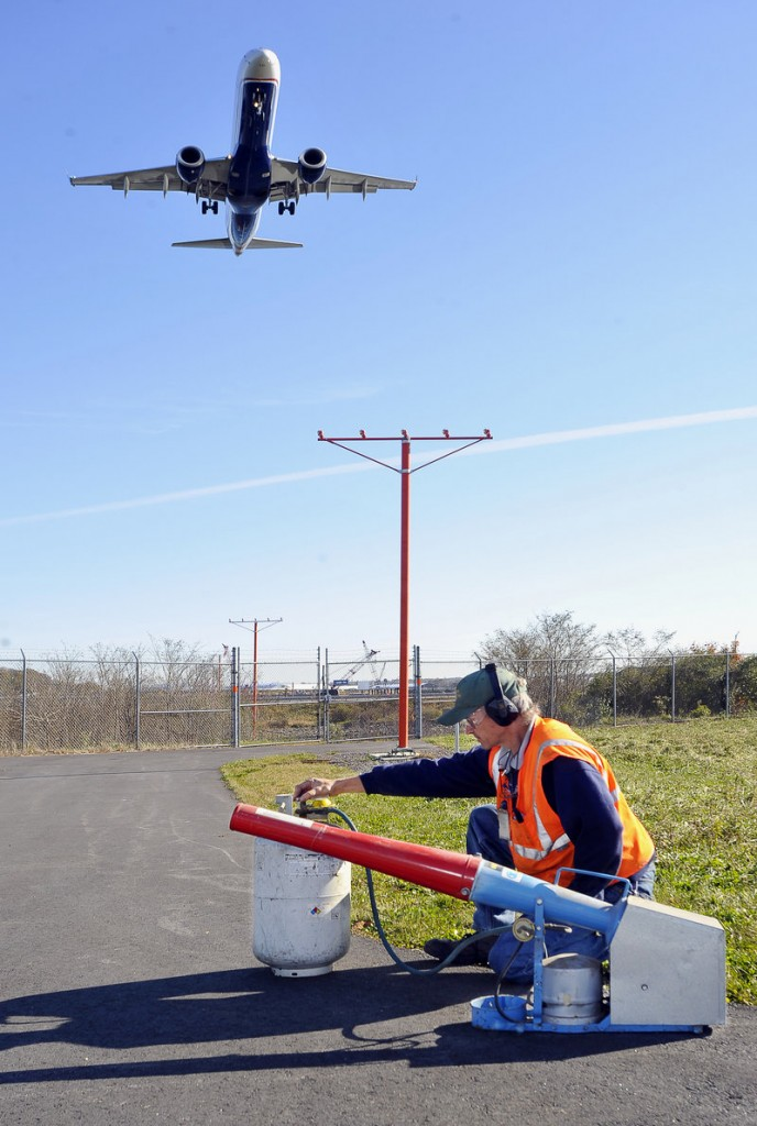 Keith Lynds, a maintenance worker at the Portland International Jetport, demonstrates a propane-powered noise cannon used to scare away birds by emitting a rifle-like blast.