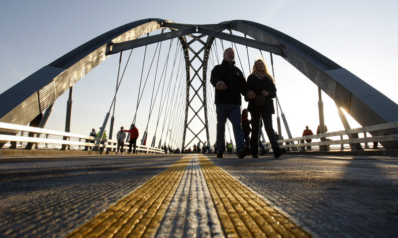 Pedestrians cross the Lake Champlain Bridge after a dedication ceremony Monday in Crown Point, N.Y. The original span was closed in 2009 after it was deemed unsafe. The bridge reconnects Crown Point and West Addison, Vt.