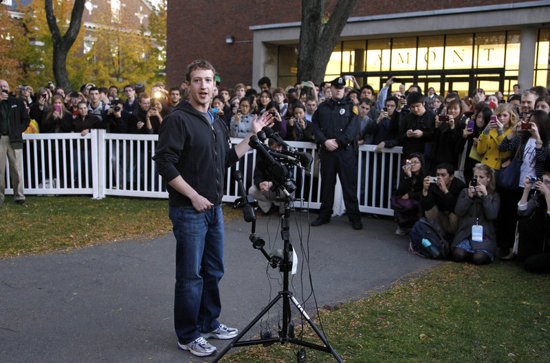Facebook creator Mark Zuckerberg takes questions from members of the media as a crowd watches from behind temporary barriers on the campus of Harvard University in Cambridge, Mass., on Monday.