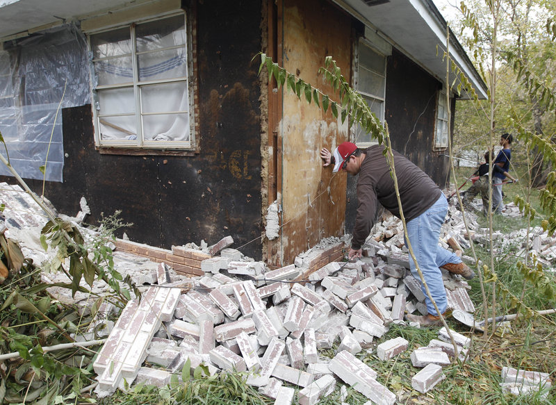 A man works Sunday to clear away bricks that fell from his in-laws' home in Sparks, Okla., during Saturday's earthquake. Experts say the quakes were natural, not the result of drilling.