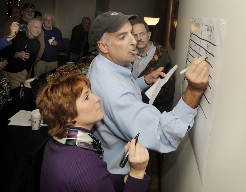 Laura and Randy Seaver post results at election night headquarters for mayoral candidate Alan Casavant at the North Dam Mill in Biddeford.