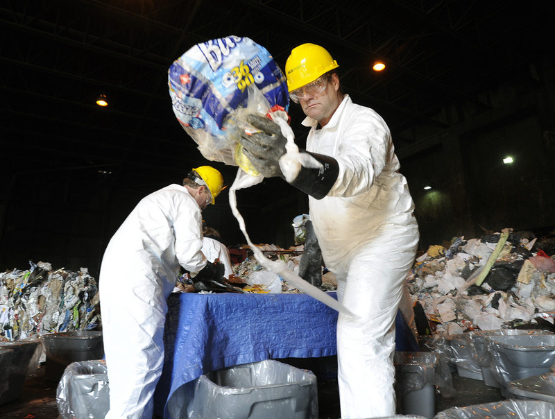 Darrell Seekins, one of the crew hired to sort trash Wednesday for a University of Maine study on recycling, separates Scarborough trash at the ecomaine waste plant in Portland.
