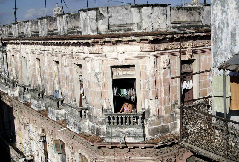 A woman looks out from an old building in Havana Friday. Cubans will now be able to buy and sell homes, President Raul Castro has delivered on his major promise this year to relax the government's grip on the economy.