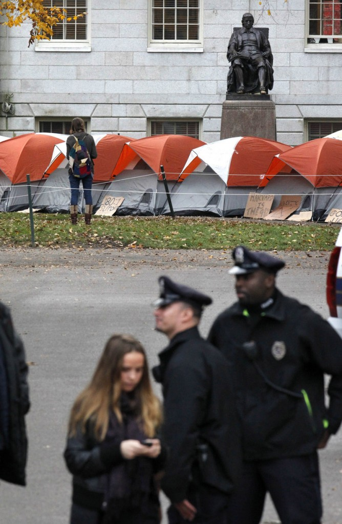 A cluster of tents sits near a statue of Harvard University founder John Harvard as police stand at an entrance to the campus in Cambridge, Mass., on Thursday.
