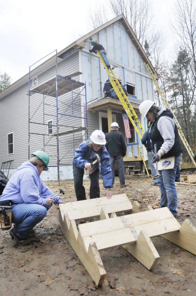From left, Pat Iles of Brunswick, who served in the Navy, LaRhonda Harris of Jefferson, who served in the Air Force, and Jasmine Savoi, who works at the Veterans Center in Lewiston, work together to help Habitat for Humanity build homes in Freeport on Friday.