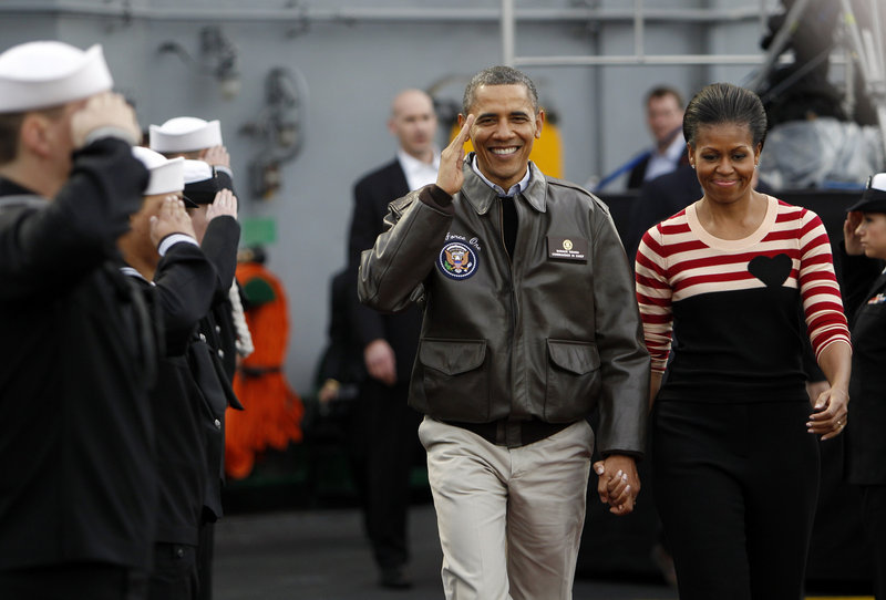 President Obama and first lady Michelle Obama walk on the flight deck of the USS Carl Vinson for the Carrier Classic NCAA college basketball game Friday in Coronado, Calif.