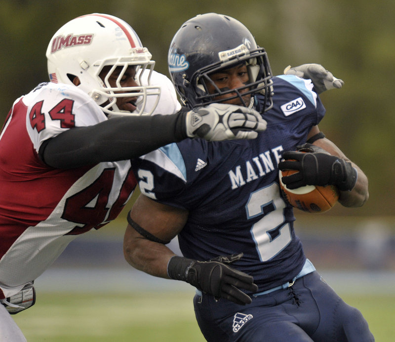 Pushaun Brown of Maine eludes a tackle by Perry McIntyre of Massachusetts and scoots into the end zone for a first-half touchdown Saturday, helping the Black Bears to a 32-21 victory. Maine and Towson are tied atop the CAA.