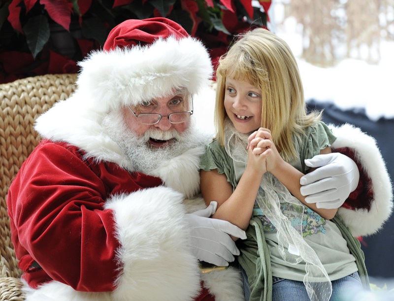 Jianna Sperdakos, 7, of Hebron visits with Santa at the Maine Mall on Saturday. The mall is back to full capacity, and its management expects that new stores there will boost shopping traffic this holiday season.