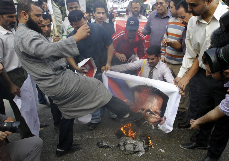 A Syrian protester kicks a burning picture of Syrian President Bashar Assad during a protest in front of the Arab League headquarters in Cairo on Saturday.