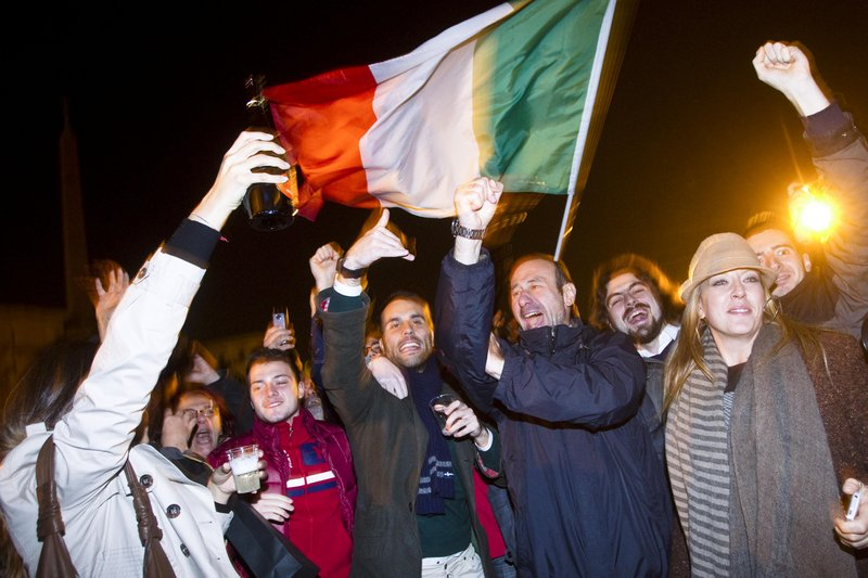 An Italian flag unfurled above them, people celebrate the resignation of Premier Silvio Berlusconi in Rome on Saturday. The beleaguered prime minister ended a 17-year political era and set in motion a transition aimed at bringing Italy back from the brink of economic crisis.