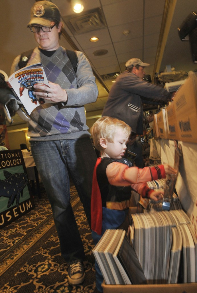 Josh Lovejoy, left, of South Portland looks over trade paperbacks as his son, Eamon, 2, dressed as Thor, plays with an action figure.