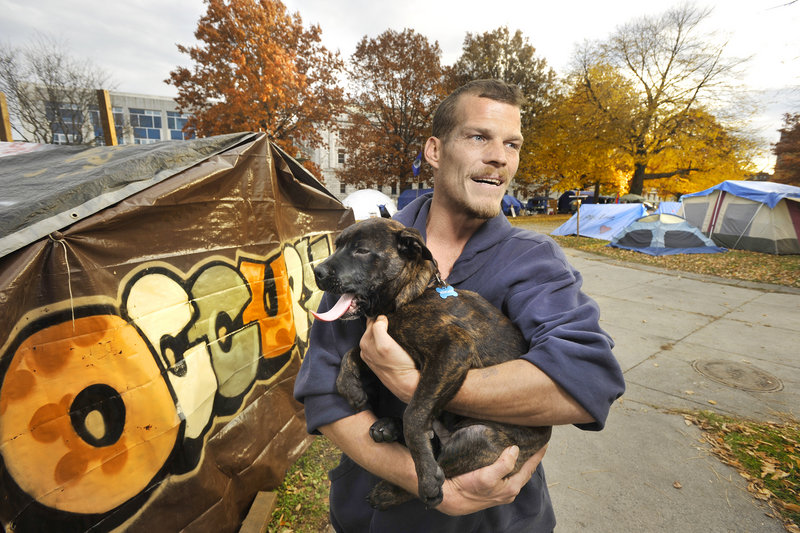 """""""From my understanding, there (won't) be any movement against Occupy Maine in Lincoln Park unless there's a health or safety issue,"""" Chris Schisler said. His dog, Boss, is the unofficial camp mascot."""