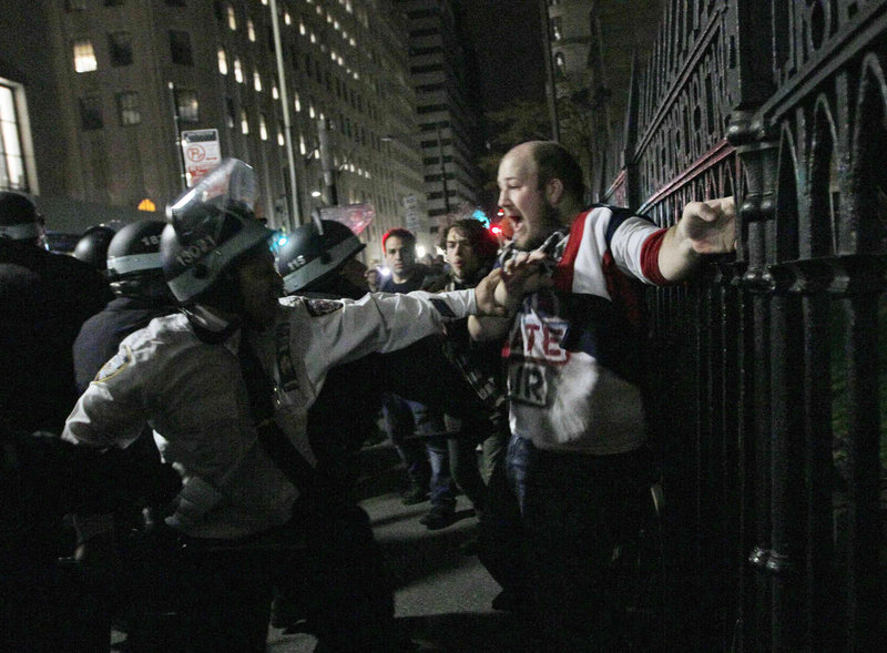Protester Brent Schmidt of Brooklyn, N.Y., is arrested near the Occupy Wall Street encampment at Zuccotti Park in New York early Tuesday. Police handed out notices saying the park had to be cleared because it was unsanitary and hazardous.