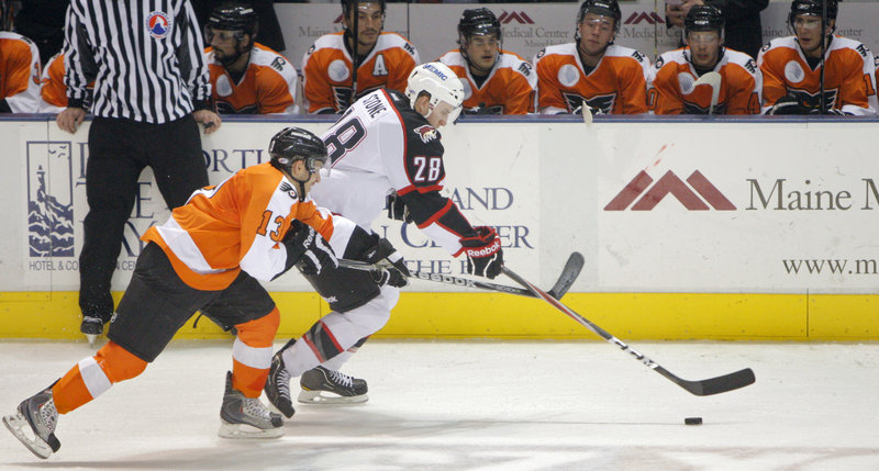 Michael Stone of the Portland Pirates brings the puck in front of the Philadelphia bench as Garrett Roe of the Phantoms gives chase.