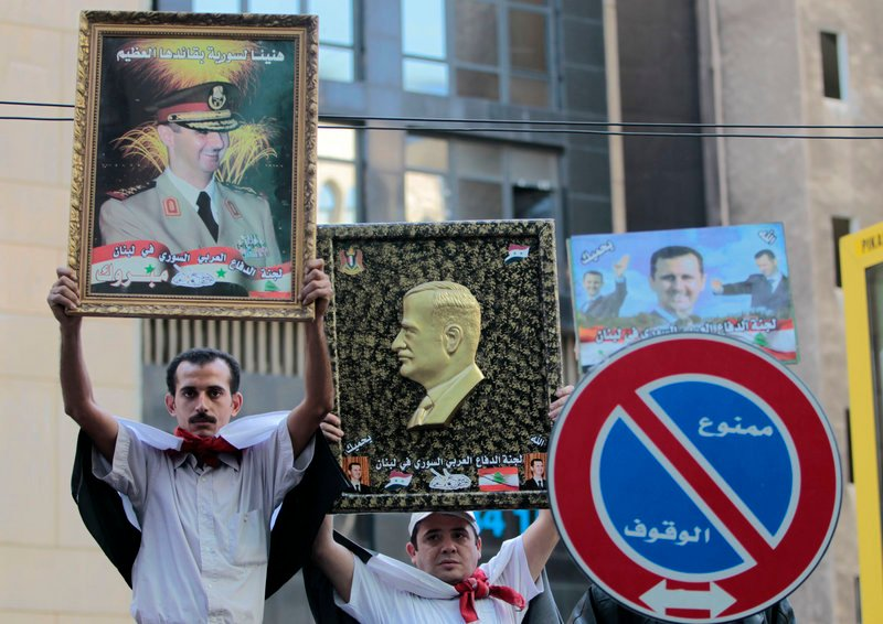 Pro-Syrian regime protesters in Beirut, Lebanon, hold up portraits of Syrian President Bashar Assad, left, and his father, Hafez Assad, right, during a demonstration against the Arab League decision to suspend Syria earlier this week.