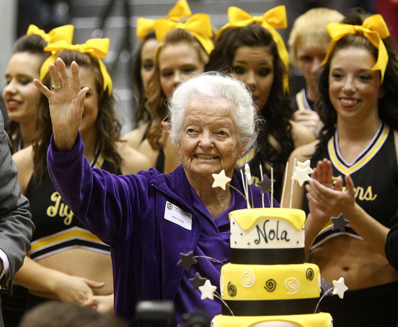 Nola Ochs, center, of Jetmore, Kan., celebrates her 100th birthday with friends, family and cake during halftime of the Fort Hays State University men's basketball game in Hays, Kan., on Tuesday. Ochs' actual birthday is next week.