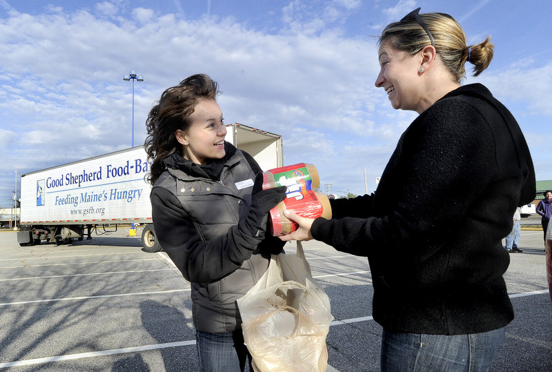 Lisa Kendrick, right, of Kennebunk gives food products to Clara McConnell, communications manager with the Good Shepherd Food-Bank, during a food-collection event at the Maine Mall in South Portland on Saturday.