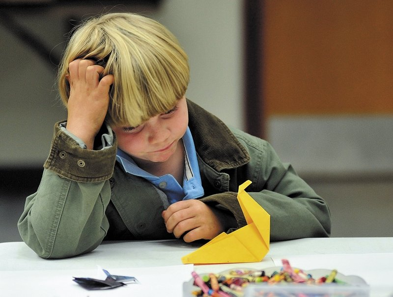 Seven-year-old Danny Taylor ponders his next move as he works on an origami crane as part of a project at the Starks Community Center.