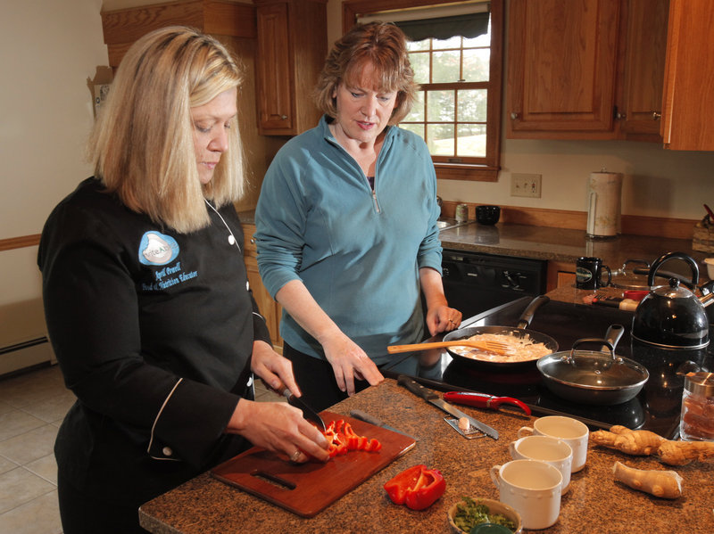 April Powell, left, teaches Marcia Scott how to make simple ginger curry chicken at Scott's home in Arundel. Powell runs a company called InviteAbitE, which helps clients shop for and cook with nutrient-dense whole foods. Scott competes in triathlons and was looking for meals that would work well with her training.