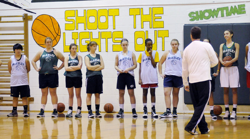 The McAuley girls' basketball team listens to Coach Bill Goodman Monday at the start of the first practice. The Lions' opener is Dec. 9.