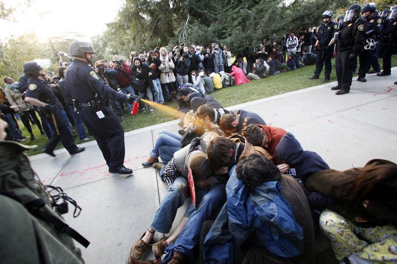 University of California, Davis police Lt. John Pike uses pepper spray to move Occupy UC Davis protesters while blocking their exit from the school's quad Friday.