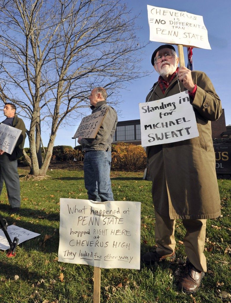"""Bill Slavick, right, and Rick Romano protest at Cheverus High. Slavick wears a sign saying, """"Standing in for Michael Sweatt,"""" who has said he was sexually abused at the school long ago."""