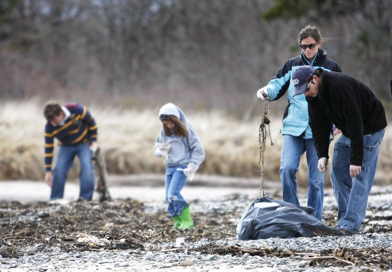 Volunteers pick up trash on Crescent Beach on Earth Day last year. A reader applauds a Girl Scout who called attention to widespread littering.