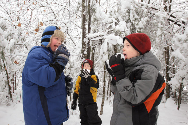 Youngsters, from left, Anthony Esposito, Jacob Coughlin and Casey Coughlin, get a taste of winter outside the Coughlin home in Limington on Wednesday after the second nor'easter of the season.