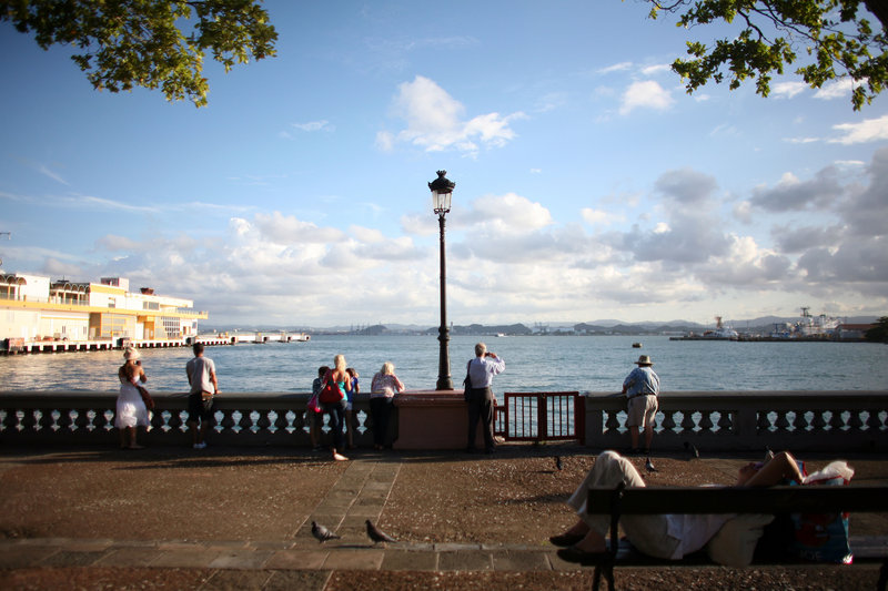Tourists look out from the pier near the cruise ship terminal in Old San Juan, Puerto Rico, on Wednesday. The Caribbean anticipates another surge in visitors this winter, but officials warn that the amount the average tourist spends probably will decline.