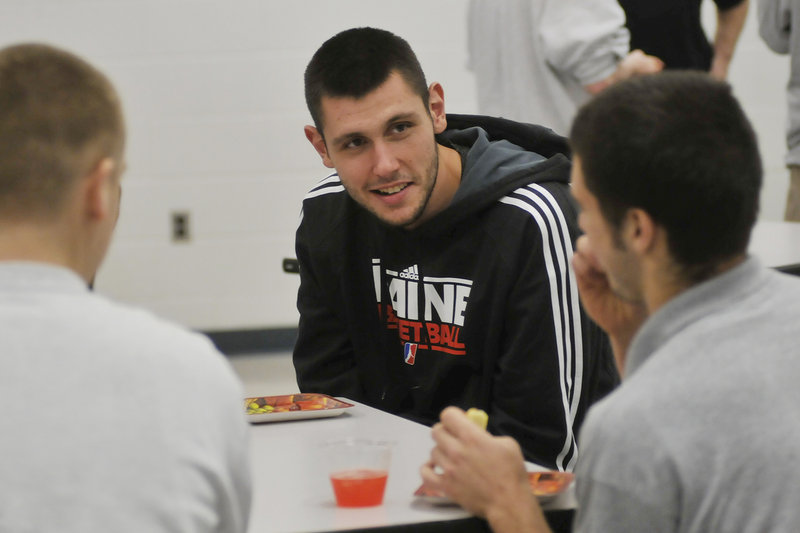"Mike Tisdale of the Red Claws talks with a youth center resident Thursday. One resident was amazed to learn that Tisdale wears a size-18 shoe. ""It's a freakin' boat,"" said Alex Pedroza."