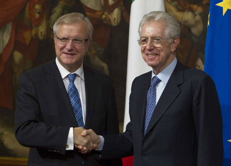 European Commissioner for the Economy Olli Rehn, left, shakes hands with Italian Premier Mario Monti as they meet in Rome on Friday. The Italian government is trying to convince investors that can successfully reduce debt.