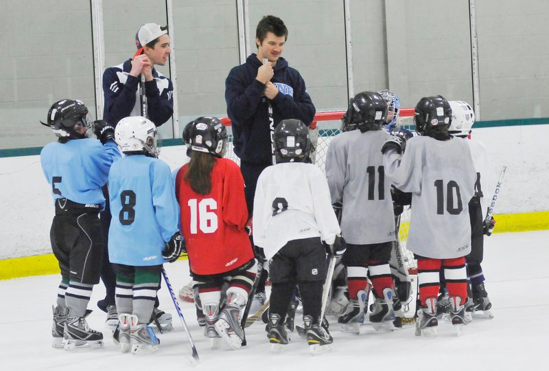University of Maine goaltenders Martin Ouellette, left, and Dan Sullivan talk with young players Friday during a clinic at Family Ice Center in Falmouth. The Black Bears will play Clarkson tonight at the Cumberland County Civic Center.