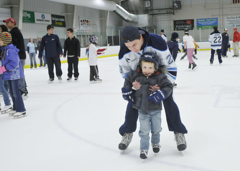 Kieran MacDonald, a 3-year-old from Levant, gets a little help skating from Connor Leen of the University of Maine during public skating time.