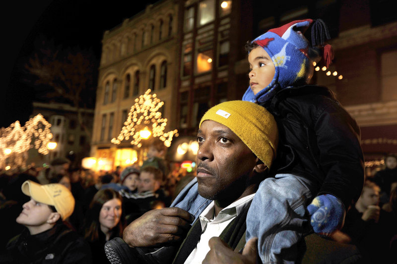 Kazmir Bickens, 2, sits on the shoulders of his dad, Louis, during the tree lighting ceremony.