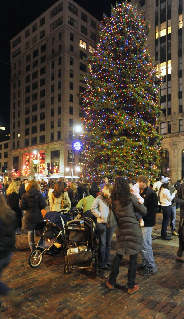 The Christmas tree lights up Monument Square.