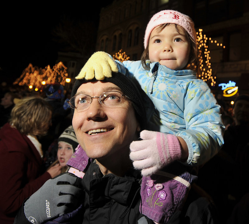Bob Bukaty of Freeport and his daughter, Bella, watch as the Christmas tree is lit in Monument Square.