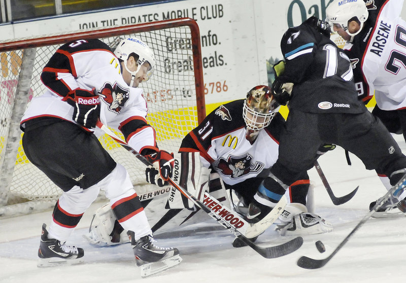 Portland goalie Curtis McElhinney keeps his eye on the puck Friday night as it bounces in front of the net and Tommy Wingels of the Worcester Sharks tries to put it in. Chris Summers, left, and Dean Arsene help on defense.
