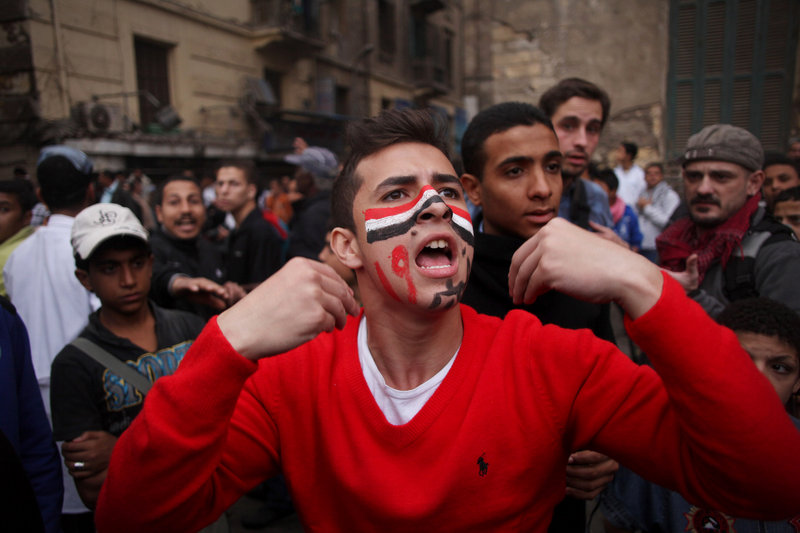 A protester with the colors of Egypt's flag on his face joins tens of thousands of others Friday near Tahrir Square in Cairo.