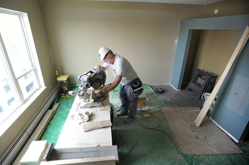 Finish carpenter Eugene Rogers cuts trim in a studio apartment at Oak Street Lofts in Portland. The units are small, roughly 400 square feet.