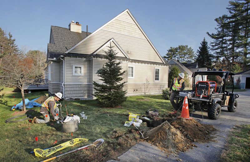 Justin Desrosiers, left, and Joe Jones install a natural gas line at Botany Place condominiums in Brunswick in 2014.