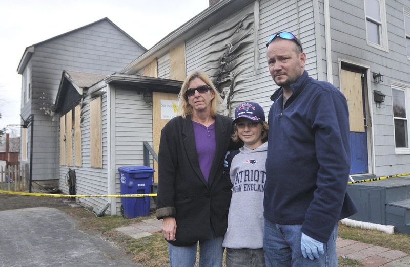 The Calkins family — Denise, 10-year-old Max and Mark — stand outside their fire-damaged home. Not pictured is son Sam Lennon, 16. A fund has been set up at Saco & Biddeford Savings Institution to aid the family in their recovery.