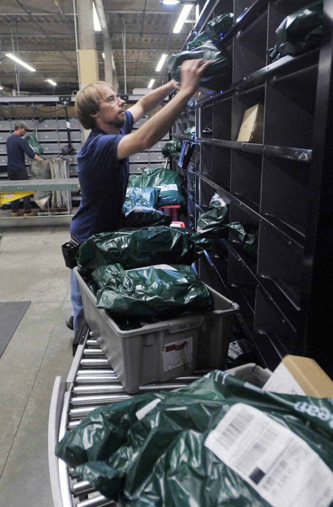 Ron Hills sorts L.L. Bean products by ZIP codes for shipping on Monday. The Freeport-based retailer hired about 4,700 seasonal workers this fall, mostly to answer phones or online questions in customer service centers.