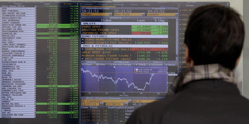 A man checks stock indexes on a screen of a bank in Milan, Italy, on Monday. Italy paid sharply higher borrowing rates in an auction Monday, as investors continued to pressure the eurozone's third-largest economy to come up with reforms.
