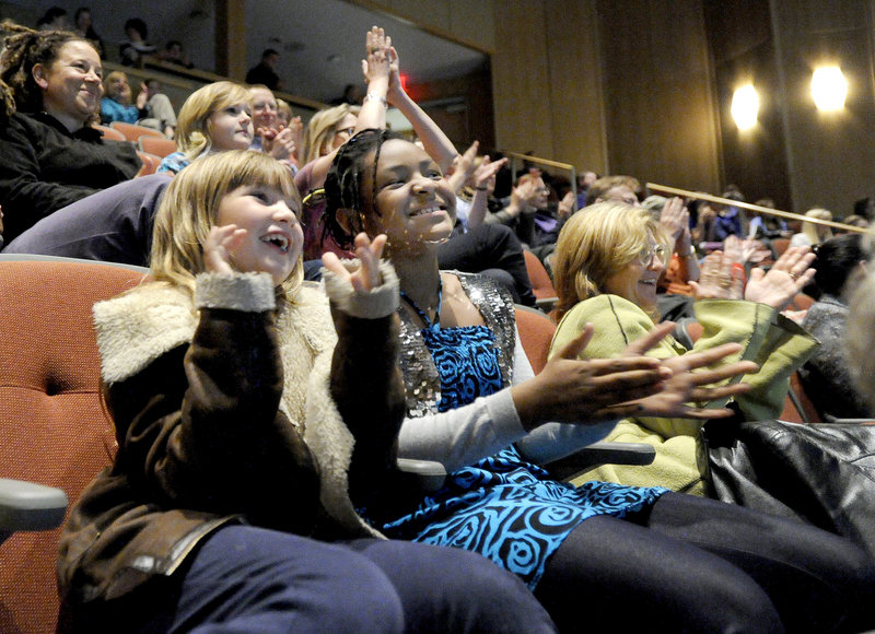 "Laura Martin, 8, and Grace McCollum, 9, of Portland watch Waynflete graduate Michael Odokara-Okigbo and his group, the Dartmouth Aires, on ""The Sing-Off"" finals Monday night with a crowd of supporters in the school's Franklin Theater."